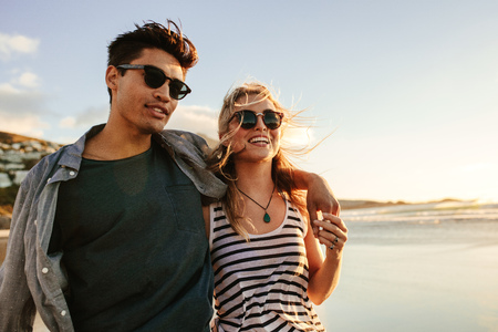 Portrait of handsome young man with his beautiful girlfriend on beach. Young couple enjoying a summer day on seashore. Archivio Fotografico