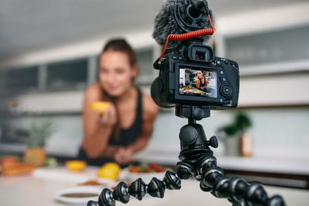 Young woman recording video on tripod mounted camera in kitchen. Camera showing woman with an orange in hand.