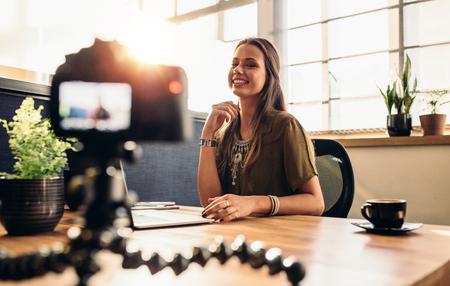 Joven mujer de grabación de vídeo para su vlog en una cámara digital montada en trípode flexible. Sonriente mujer sentada en su escritorio trabajando en un ordenador portátil. Foto de archivo - 74776433