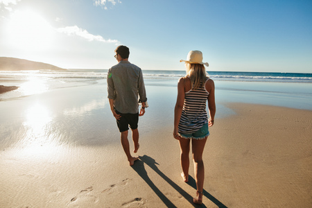 Rear view shot of young man and woman walking on seashore. Couple on beach holiday in summertime.