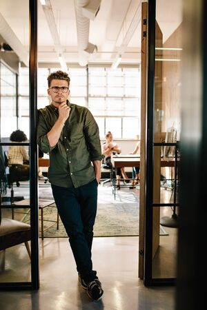 millennial: Full length portrait of handsome young man standing in doorway of office with people working in background.