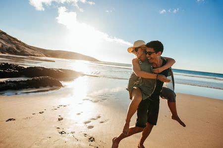 로맨틱 젊은 부부 여름 휴가 즐기기. 해변에서 여자 친구에 게 피기 백 탐을주는 잘 생긴 젊은 남자.