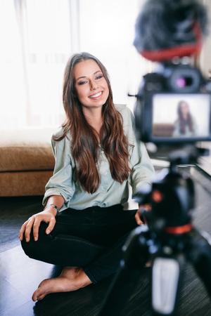 Jonge vrouwelijke vlogger op het camera scherm. Glimlachende vrouw zittend op de vloer opnemen haar inhoud.