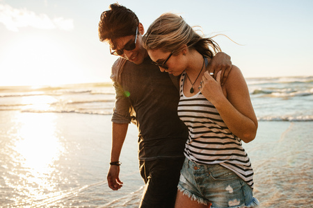 Young couple walking on the seashore. Man and woman in love on the beach during sunset.