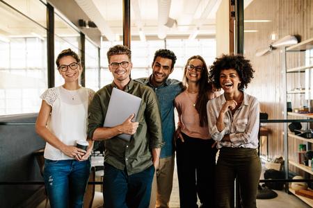 함께 서서 웃 고 창조적 인 비즈니스 팀의 초상화. Multiracial 비즈니스 사람들이 함께 시작.