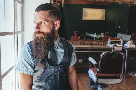 Ritratto di barbiere con finestra in piedi grembiule e guardando lontano. Parrucchiere maschile guardando fuori dalla finestra e pensando. Archivio Fotografico - 75087534