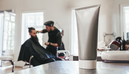 cutting: Shaving cream tube on counter with barber serving client in background. Stock Photo
