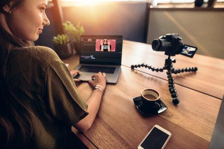 Jonge vrouw kijkt naar camera tijdens het werken op laptop. Jonge fotograaf met haar camera en laptop op haar bureau.