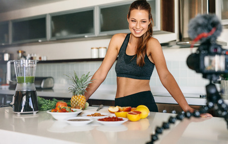 tripod mounted: Smiling woman preparing a healthy breakfast with fruits and vegetables. Young lady standing at the kitchen table looking at a camera mounted on tripod. Stock Photo