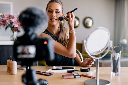 online: Young lady recording her video while applying cosmetics. Woman making a video for her blog on cosmetics. Stock Photo