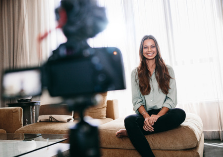 tripod mounted: Young woman recording video on camera mounted on a tripod for her vlog. Pretty woman smiling at the camera sitting in her living room.