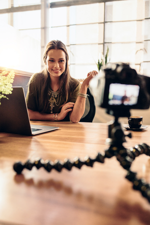 Young woman recording video for her vlog on a digital camera mounted on flexible tripod. Smiling woman sitting at her desk working on a laptop computer looking at the camera. Imagens
