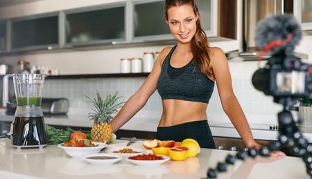 三脚にカメラを見て台所のテーブルで立っている若い女性。果物と野菜で健康的な朝食を準備する女性。