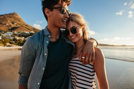 Outdoor shot of loving young couple walking on beach. Young happy man and woman strolling together on seashore.
