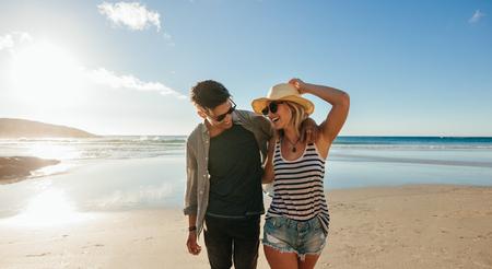 Horizontale schot van gelukkig jong koppel op het strand. Jonge man en vrouw lopen op zee en lachen.