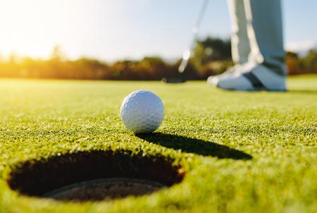 Professionele golfer zetten bal in het gat. Golfbal aan de rand van het gat met speler in de achtergrond op een zonnige dag. Stockfoto