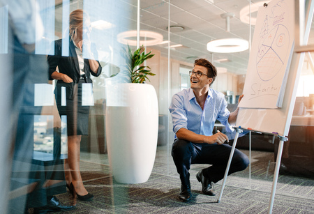 Gelukkige rijpe Kaukasische zakenman dichtbij tikraad met diagram. Beambte die een presentatie op een flip-over geeft aan collega's en het glimlachen. Stockfoto
