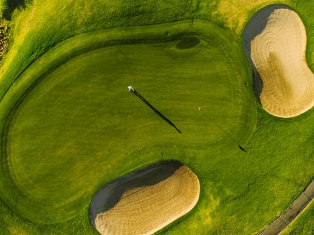 ゴルフ場のグリーンの選手の空中写真。ゴルファーはパッティング グリーンで夏の日の演奏します。