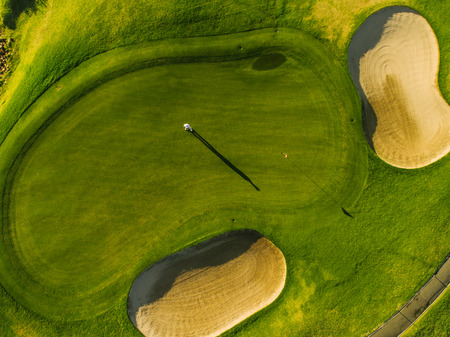 Aerial view of players on a green golf course. Golfer playing on putting green on a summer day. Stock fotó