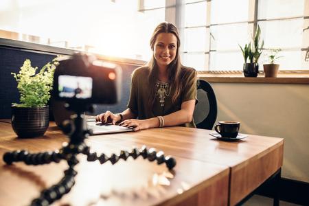 유연한 삼각대에 탑재 된 디지털 카메라에서 동영상 블로그를 녹화하는 젊은 여성 비디오. 랩톱 컴퓨터에서 작업하는 그녀의 책상에 앉아 웃는 여자. 스톡 콘텐츠