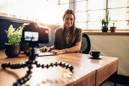 Junge Frau Aufnahme Video für ihre Vlog auf einer Digitalkamera auf flexiblem Stativ montiert. Lächelnde Frau sitzt an ihrem Schreibtisch arbeiten an einem Laptop-Computer. Standard-Bild - 75829692