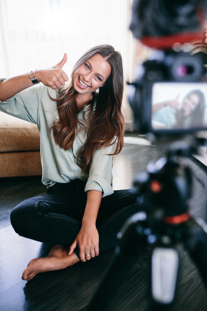 Young vlogger showing thumb up sign recording her videoblog. Smiling woman sitting on floor recording content on camera. 写真素材