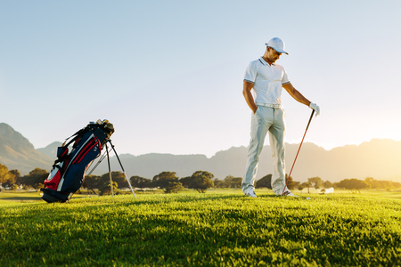 Full length of young man standing on golf course at sunset. Professional male golfer holding golf club on field. Stock Photo