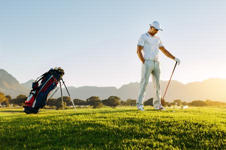 Longitud total de joven parado en el campo de golf al atardecer. Golfista masculino profesional que detiene al club de golf en campo. Foto de archivo - 75829704