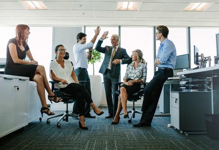 두 쾌활 한 비즈니스 사람들이 높은 5 그들의 동료를 찾고 웃 고 동안주고. 사무실에서 성공을 즐기는 비즈니스 팀
