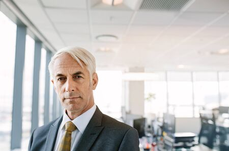 1 person: Portrait of confident mature businessman in office. Caucasian male entrepreneur in suit looking at camera with copy space.