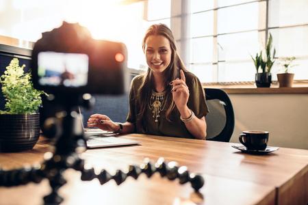 Jonge vrouw video-opname voor haar vlog op een digitale camera gemonteerd op flexibele statief. Lachende vrouw zittend op haar bureau werkt op een laptop computer.