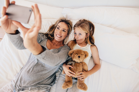 woman on phone: Mother and daughter lying on bed and taking self portrait with mobile phone. Woman taking selfie with a little girl holding teddy bear in bed.