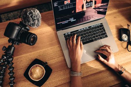 Vue de dessus de la vidéo d'édition de vlogger féminine sur ordinateur portable. Jeune femme travaillant sur ordinateur avec un café et des caméras sur table. Banque d'images