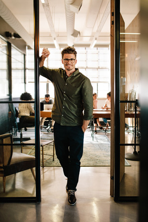 Full length portrait of happy young businessman standing in doorway of office. Caucasian male executive in office with people working in background. Stock Photo