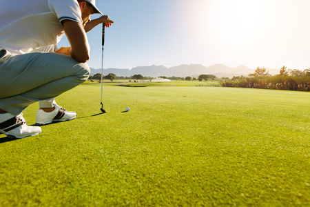 Pro-Golfspieler, der Schuss mit Club auf Kurs anstrebt. Männlicher Golfspieler auf ungefährem Putting Green, zum des Schusses zu nehmen. Standard-Bild
