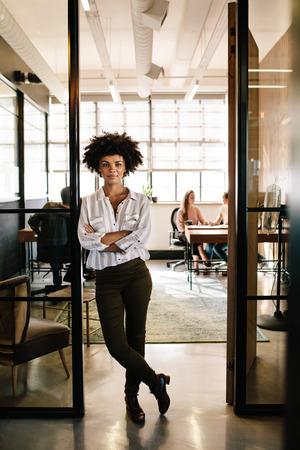 Portrait de pleine longueur de jeune femme confiante debout dans la porte du bureau avec les bras croisés. Exécutif féminin au démarrage avec des personnes travaillant en arrière-plan. Banque d'images - 76464937