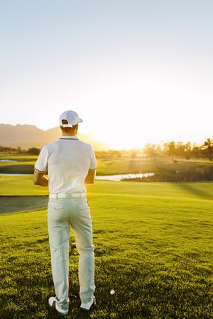 Retrovisione di giovane giocatore di golf maschio che sta al quadrato del T sul corso. Giocatore di golf maschio professionale che gioca un giorno soleggiato. Archivio Fotografico - 76483112