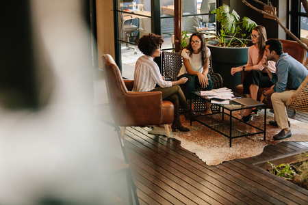 Corporate professionals meeting in office lobby. Creative people doing a brainstorming meeting in a modern office Stock Photo