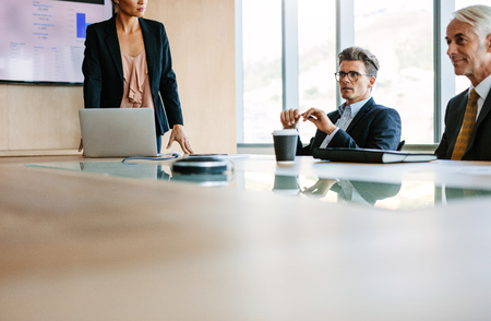 Businesspeople sitting at board room and discussing new strategies. Businessman and businesswoman meeting in conference room Stock Photo