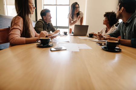 Young woman discussing with group of executives sitting around a table. Multi ethnic business team meeting in conference room.