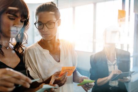 Zakenvrouwen bespreken voor de glazen muur met post-notities en stickers. Bedrijfspersoneel die lijmnotities gebruikt voor brainstormen in modern kantoor. Stockfoto