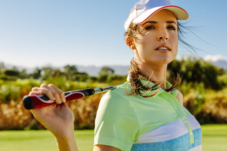 Close up portrait of attractive female golfer holding golf club on field and looking away. Young woman standing on golf course.