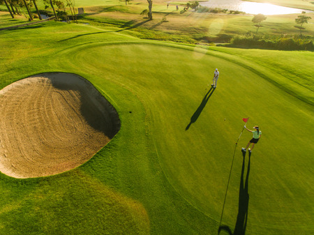 Golf course top view with players. Aerial view of golfers on putting green. Archivio Fotografico