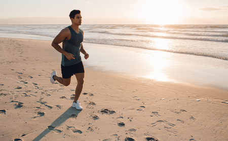 Young man on morning run outdoors on sea shore. Young man training on the beach in morning.