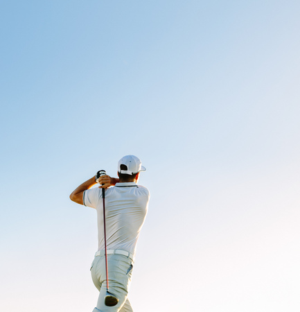 Professional golfer taking shot against clear sky. Rear view of golf player swinging golf club on sunny day.