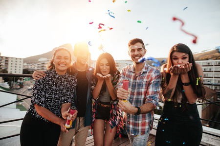 Group of friends hanging out together and blowing confetti on rooftop party.