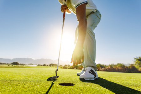 Geschossen von einem Golfspieler, der den Ball vom Loch herausnimmt. Golfspieler, der den Ball vom Loch nach erfolgreichem Setzen auswählt Standard-Bild - 76403817