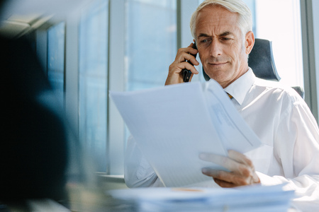 working office: Shot of senior businessman sitting at his desk reading a document and talking on phone. Mature business professional working at his office desk. Stock Photo