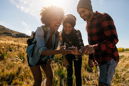 lady on phone: Group of hikers looking at pictures on mobile phone and laughing. Happy young people hiking in countryside.