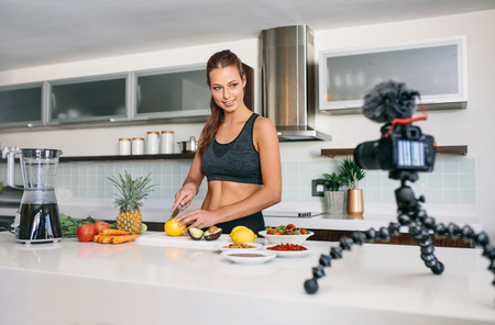 screen: Young woman recording food based video content on camera. Smiling woman cutting fruits and vegetables in kitchen. Stock Photo